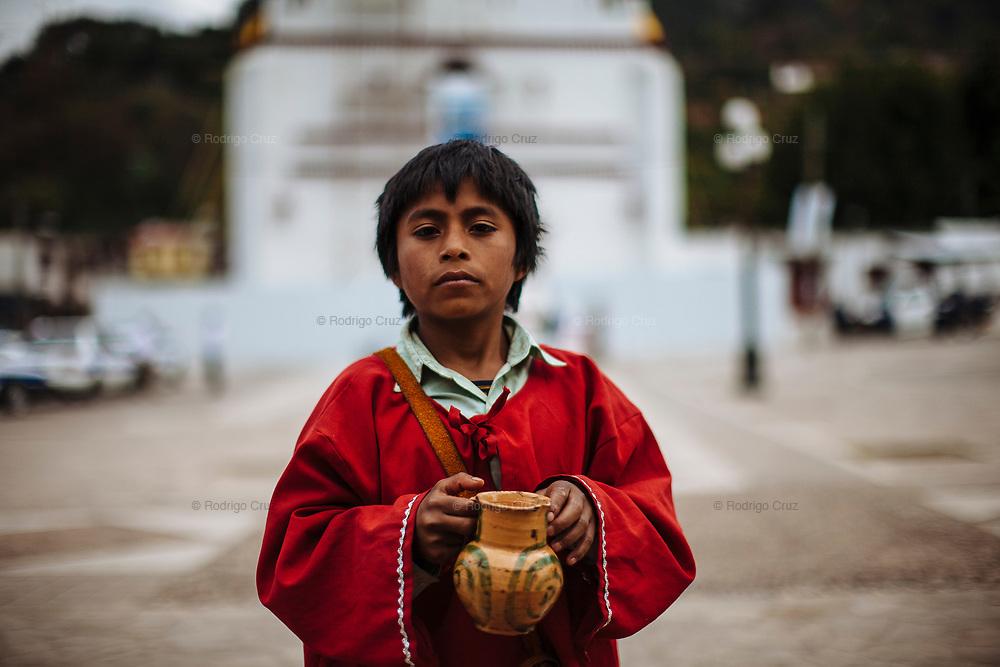 Los niños que se encargan de servir el pox, un aguardiente de caña, además de chicha, que es un fermentado de caña y endulzado con panela durante el carnaval de Tenejapa, Chiapas.