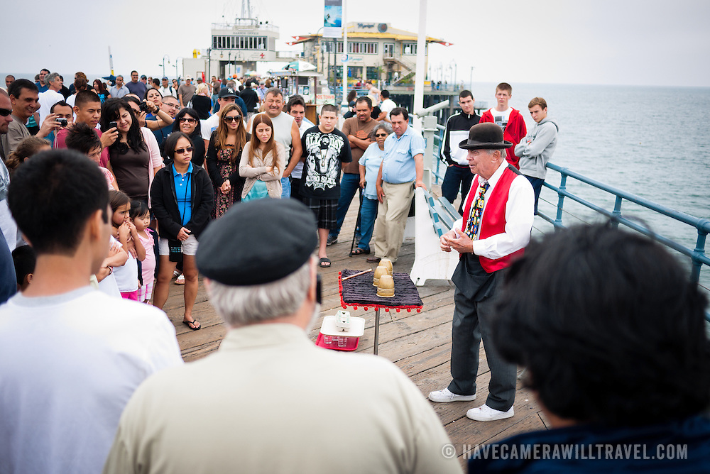 A street magician on Santa Monica pier performs a shell game for the crowd.