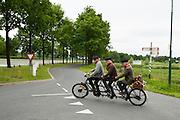 Drie Belgische deelnemers rijden op een oude triplet, een driepersoons tandem. Bij Utrecht wordt de tandemtocht gehouden. De tocht werd van 1975 tot 1982 jaarlijks gehouden en was in die tijd een groots succes. Organisator Herbert Kuner, een expert in oude fietsen, wil het nu nieuw leven inblazen. In totaal rijden dit jaar vijftien tandems mee. Tijdens de route van 40km rondom Utrecht hoeven de fietsers slechts zes verkeerslichten te passeren.<br /> <br /> Three men of Belgium ride a three person tandem. In Utrecht, the tandem tour is held. The tour was held annually from 1975 to 1982 and at that time was a grand success. Organizer Herbert Kuner, an expert in old bikes, wants to restart the tradition. In total this season, with fifteen tandems. During the route of 40km around and Utrecht cyclists passing only six traffic lights.