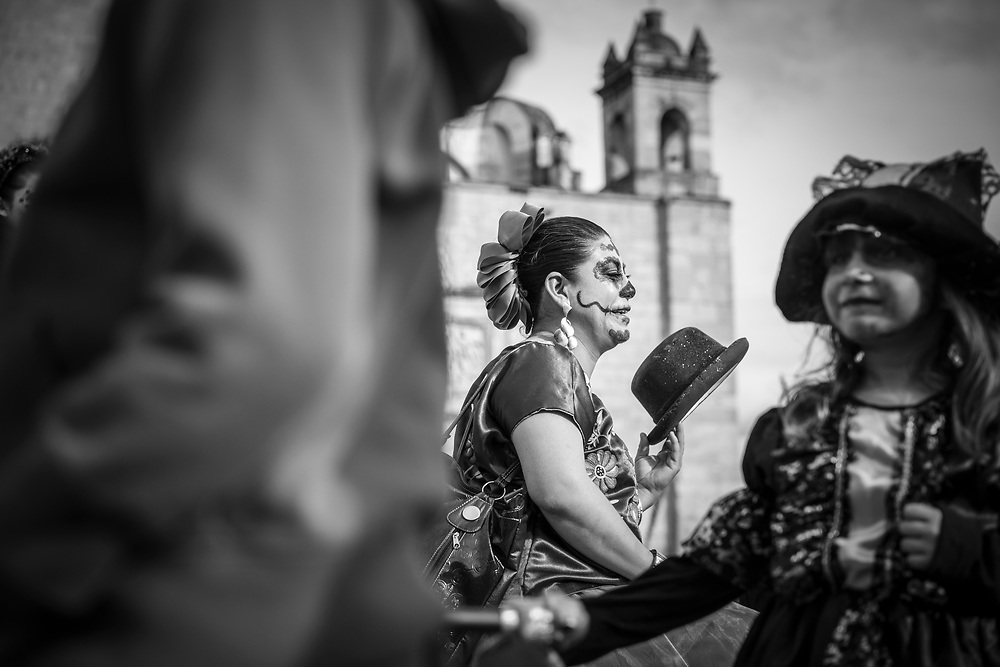 """A Mexican woman sits in a crowd outside the Church of Santo Domingo de Guzmán in Oaxaca; Mexico. She and others are dressed for Day of the Dead celebrations (""""Día de los Muertos"""" in Spanish)."""