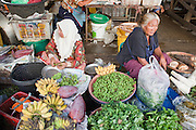 """Sept 25, 2009 -- PATTANI, THAILAND: A Muslim woman (left) and a Thai Buddhist woman work as vendors in the morning market in Pattani, Thailand. Thailand's three southern most provinces; Yala, Pattani and Narathiwat are often called """"restive"""" and a decades long Muslim insurgency has gained traction recently. Nearly 4,000 people have been killed since 2004. The three southern provinces are under emergency control and there are more than 60,000 Thai military, police and paramilitary militia forces trying to keep the peace battling insurgents who favor car bombs and assassination.  Photo by Jack Kurtz"""