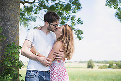 Mid adult couple kissing at each other in front of tree in the countryside, Bavaria, Germany