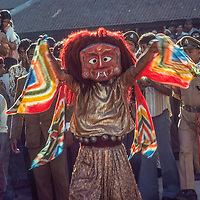 Crowds surround a masked dancer and mounted policeman at a festival in Kathmandu, Nepal.
