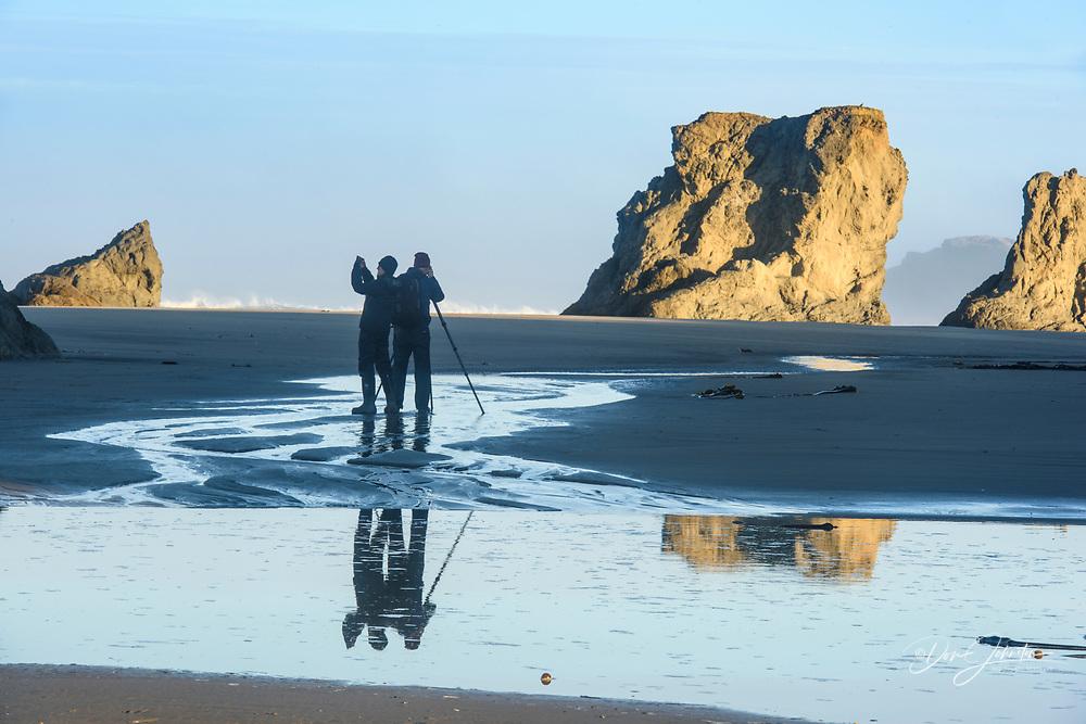 Photographers and Sea stack rocks at Bandon Beach at low tide, Bandon, Oregon, USA