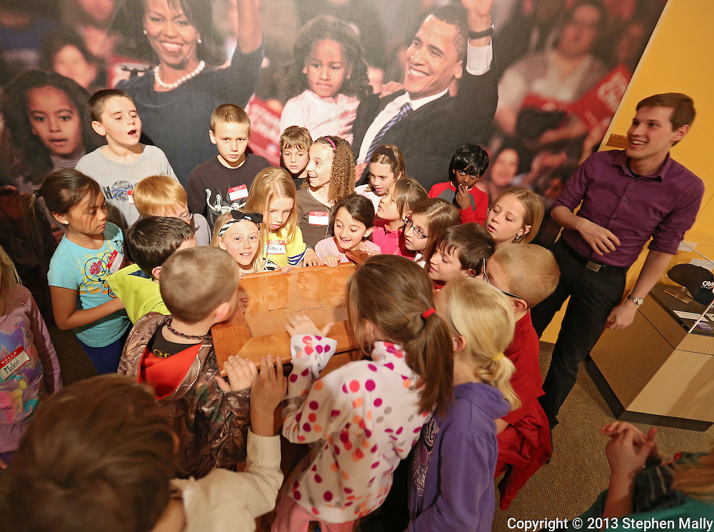 Students from Westfield Elementary School gather around to see the signature of President Barak Obama on a podium which he used on his 2008 campaign stops in Iowa as Grant Stevens, Development Director, looks on in the Endless Possibilities exhibit at the African American Museum of Iowa in Cedar Rapids on Friday, March 22, 2013.