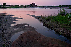 Stock photo of the silhouette of Eagle Rock at sunset along the quiet banks of the Llano River in the Texas Hill Country
