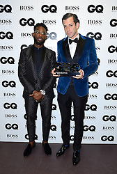 Tinie Tempah (left) presents Mark Ronson with the award for Hugo Boss Most Stylish Man in the press room at the GQ Men of the Year Awards 2016 in Association with Hugo Boss held at The Tate Modern in London. PRESS ASSOCIATION Photo. Picture date: Tuesday September 6, 2016. See PA story SHOWBIZ GQ. Photo credit should read: Ian West/PA Wire