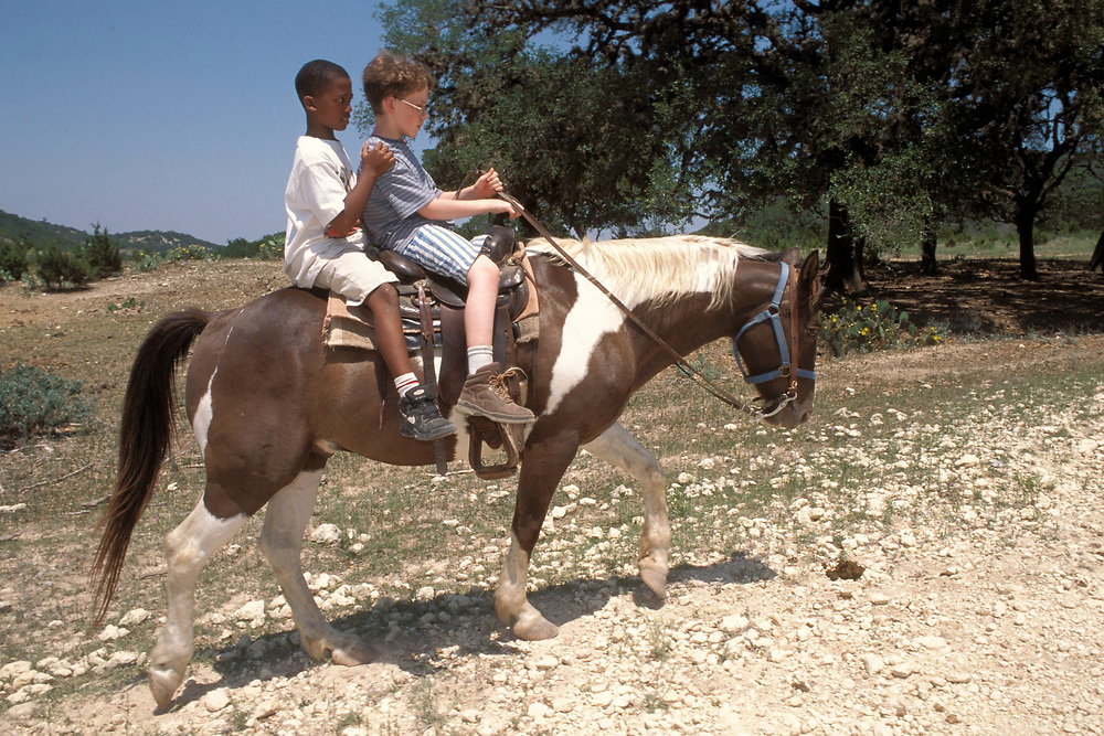 African-American and Anglo 5th grade boys  horseback riding on same horse at Outdoor Education Camp in Bandera, Texas. Model Release.<br /> ©Bob Daemmrich