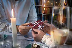 Romantic couple exchanging gift at candlelight dinner