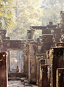 A young girl sits in a door way in the Bayon temple at Angkor, Siem Reap Province, Cambodia