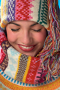 Close up of young woman wearing colorful knit winter scarf and cap with eyes closed