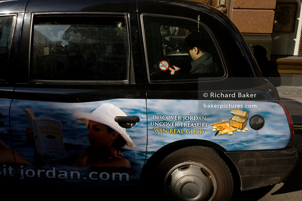 A Jordan holiday advert on the side of a London taxi cab and its busy passenger who texts with a smartphone in the back.