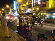 A street seller looking for customers while night tim etraffic rushes by. The tourist area of Phnom Penh, near the river.