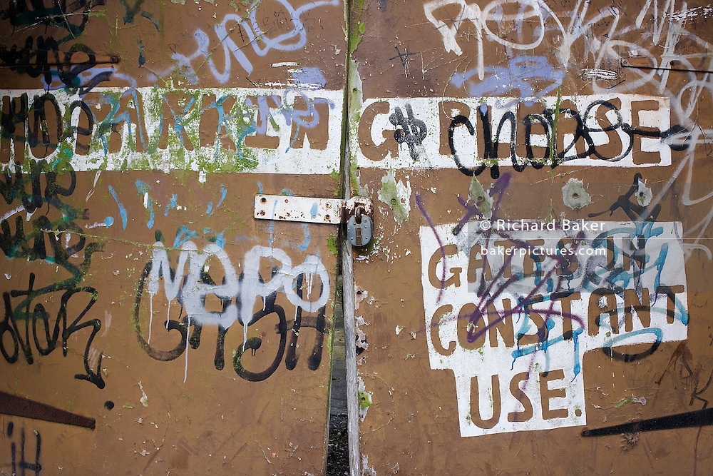 A makeshift sign on a gate with graffiti tells car drivers not to park infront of a house's driveway in Sydenham, South London.