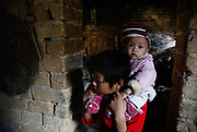 A young boy carries his baby brother on his shoulder in Caoxieping Village in Daoxian, Hunan Province, China, on Saturday, 16 October 2010. While the one child policy is strictly enforced in China's cities, the rule is much more lax in the country's vast rural areas.
