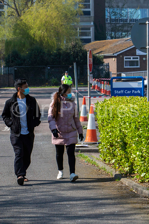 Two people wearing masks walk past the NHS staff Primary Care Clinical Assessment Centre where potentially infectious and symptomatic Coronavirus patients can be assessed and treated by a doctor or a nurse, in a safe site, on the 16th of April 2020 in Dover, United Kingdom. This is not a COVID-19 testing facility, all patients will only be clinically assessed on site as there is no community testing currently available. All patients have been referred to this centre by NHS 111 or their GP.