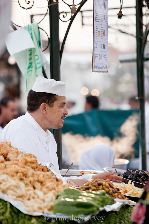 Chefs prepare food at a stall in the Djemaa el Fna in the medina of Marrakech, Morocco. Every night the main square fills with dozens of food vendors and their carts.