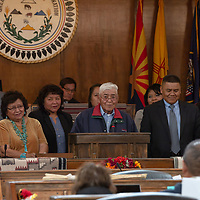 Richard Holmes, Jr., 80, is flanked on both sides by his family as they remember Leo Holmes in the Navajo Nation Council Chambers, in Window Rock.