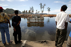 The road along the west coast came to an abrupt halt just a few kilometers from Banda Aceh where the first of many bridges had been destroyed.  Within days a simple floating raft of oil drums had been constructed and people were crossing to deliver food supplies to their families who may have stayed in their villages.<br /> The road was ripped away in many places.