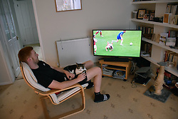 Young man watching Chelsea FC on tv during Coronavirus pandemic, UK August 2020 MR