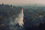 12062017 - Bel-Air, California USA:  Water is dropped by a helicopter during the Skirball Fire in Bel-Air area of Los Angeles, California. The fire, which started early Wednesday morning has burned 150 acres, destroyed 6 homes, and is 5-percent contained. Firefighters are staying in the area overnight where embers are still burning, and Santa Ana winds are expected to spread the fire. Hundreds of residents have been evacuated. (Photo by Jeremy Hogan)