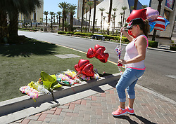 Marion Wilcox, of Hayden, Idaho, leaves balloons at a makeshift memorial on the Las Vegas Strip Tuesday, Oct. 3, 2017, in Las Vegas. Wilcox was staying in a nearby hotel when a mass shooting occurred late Sunday evening at an adjacent music festival. (Photo by Ronda Churchill/ZUMA Press)