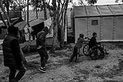 Un grupo de jovenes se dirigen a recibir alimentos de un grupo voluntario. El joven en silla de ruedas es ayudado por su hermano. Matamoros, Tamaulipas. Fotografo César Rodríguez