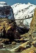 Crossing Braldu river on swing bridge en route Baltoro glacier, winter ski journey to K2