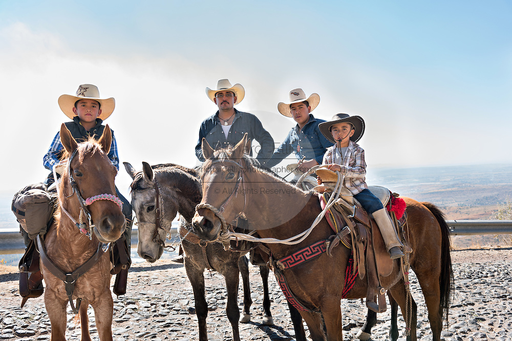 A family of Mexican cowboys pause as they ride the road up Cubilete Mountain on the final leg of the annual Cabalgata de Cristo Rey pilgrimage January 5, 2017 in Silao, Guanajuato, Mexico. Thousands of Mexican cowboys and horse take part in the three-day ride to the mountaintop shrine of Cristo Rey.