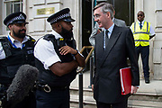Police officers speak to Jacob Rees-Mogg MP, Leader of the House of Commons as he leaves the Cabinet office in Whitehall, London, United Kingdom on 20th August 2019.