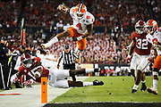 Clemson quarterback Deshaun Watson hurdles over Alabama defensive back Ronnie Harrison while leading the game-winning drive late in the fourth quarter of the College Football Playoff National Championship at Raymond James Stadium in Tampa, Florida, U.S., January 9, 2017.