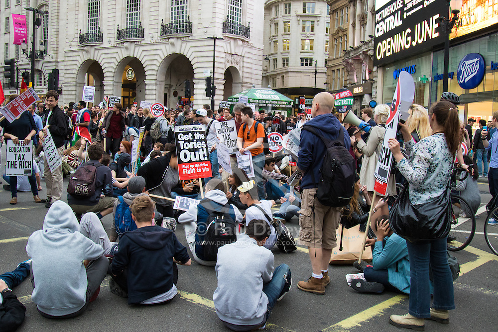 London, May 27th 2015. Protesters block traffic as they sit on the road at Piccadilly Circus during a march through the West End as they demonstrate against the Tories' ongoing campaign of austerity on the day the Queen delivered her speech to Parliament