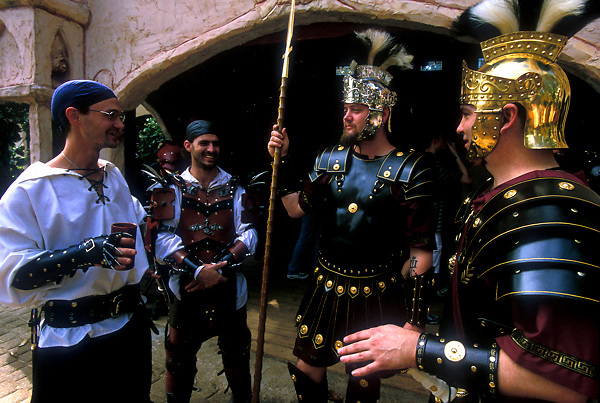Stock photo of two men dressed as armed guards talk to two other men at the Texas Renaissance Festival in Plantersville Texas