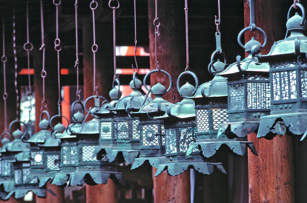 Intricately-carved metal lanterns hang in a line in Kasuga Shrine, in Nara, Japan.