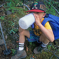 A youngster drinks water while resting during a hikes into a remote Wyoming canyon.
