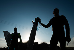 © Licensed to London News Pictures. <br /> 18/11/2014. <br /> <br /> Redcar, United Kingdom<br /> <br /> Surfers stand and look back out over the break after leaving the water following a session near Redcar in Cleveland.<br /> <br /> Photo credit : Ian Forsyth/LNP
