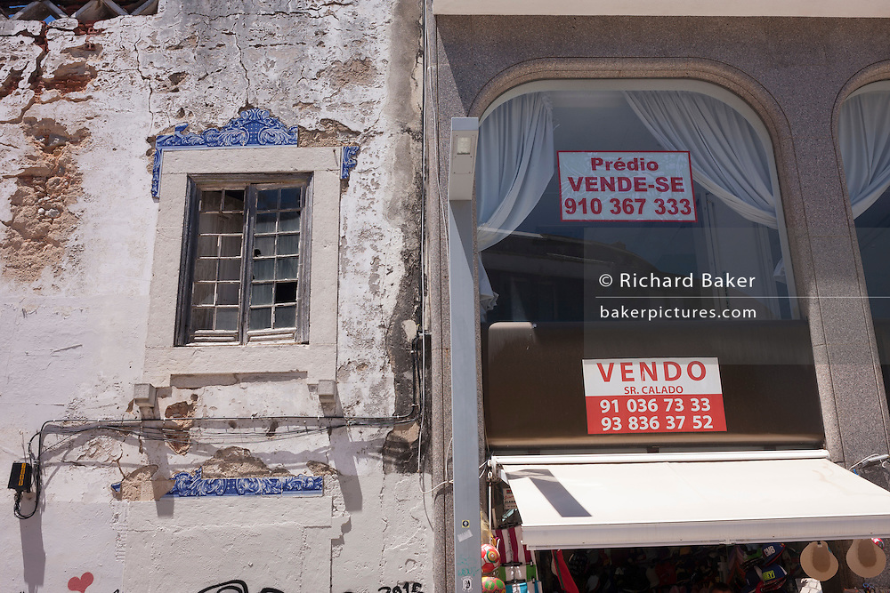 Newly restored property for sale next door to a crumbling, abandoned neighbouring house in Cascais, near Lisbon, Portugal.