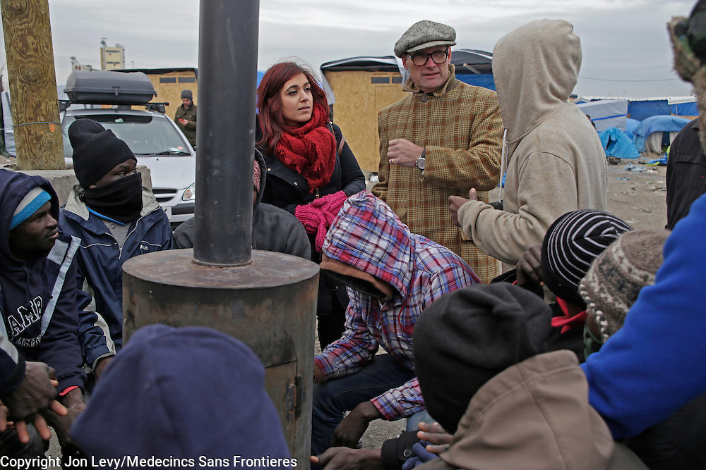 Writer AA Gill (C) and translator Bana Mina (L) talk with refugees from Darfur, Sudan, in the refugee camp in Calais France. <br /><br />Calais: AA Gill visits the refugee camps of Calais and Grande Synthe in Dunkirk.