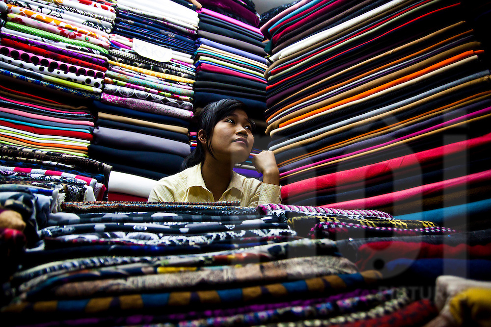 Neat stacks of colorful fabrics surround a young vendor who waits for customers in a Hanoi fabric market, Vietnam, Southeast Asia