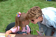 Girl whispering in mothers ear age 30 and 3. Mississippi River Carp Festival Brooklyn Park  Minnesota USA