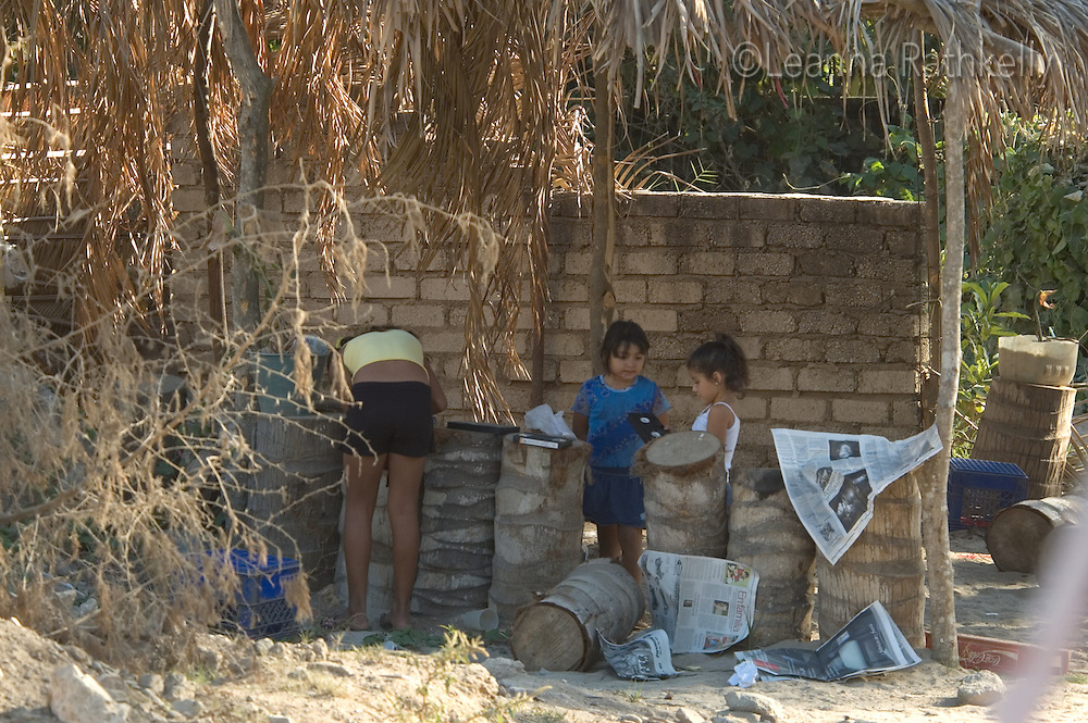 Kids play among the palm tree trunks in a construction site in Sayulita, Mexico