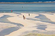 People walking on Paje Beach at low tide.  Paje, Zanzibar, Tanzania
