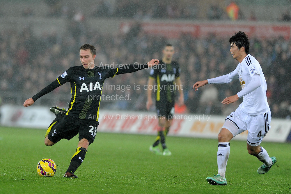 Christian Eriksen of Tottenham (l) has a shot. Barclays Premier League match, Swansea city v Tottenham Hotspur at the Liberty Stadium in Swansea, South Wales on Sunday 14th December 2014<br /> pic by Andrew Orchard, Andrew Orchard sports photography.
