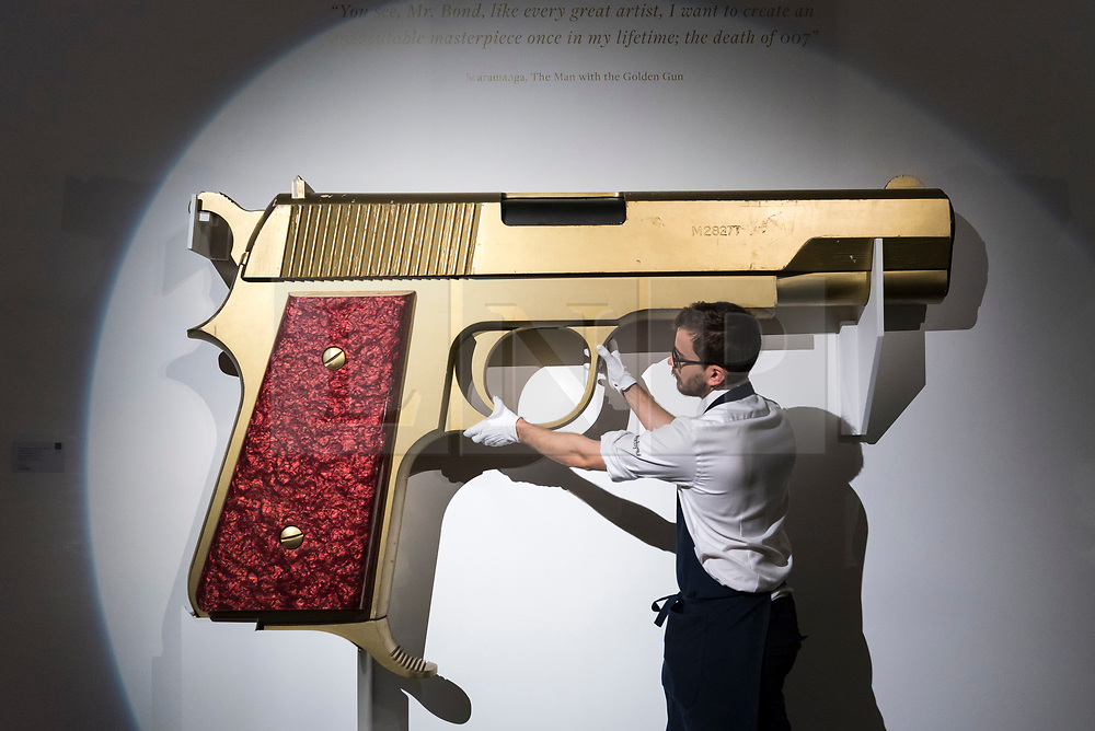 "© Licensed to London News Pictures. 25/10/2019. LONDON, UK. A technician poses with an enlarged model of 'James Bond's new gun', designed by David Collins and Floris van den Broecke for Granada Publishing Ltd., 1977 (Est. GBP3-5k).  Preview of ""GOLD: The Midas Touch"" at Sotheby's in New Bond Street.  Artworks spanning six centuries dedicated to gold will be offered for sale on 29 October.  Photo credit: Stephen Chung/LNP"