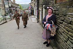 © Licensed to London News Pictures. 13/05/2016. Haworth, UK. A woman dressed in 1940s attire holds her shopping as two men dressed in home guard uniforms walk past during the annual 1940's weekend in Haworth, West Yorkshire.  Photo credit : Ian Hinchliffe/LNP