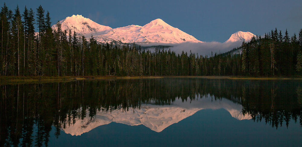 The snow covered summits of the Three Sisters are reflected in the glassy waters of Scott Lake, after an early autumn storm clears from the Oregon Cascades at sunset.