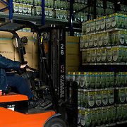 worker stacking stacks of 5 litre olive oil containers at the warehouse