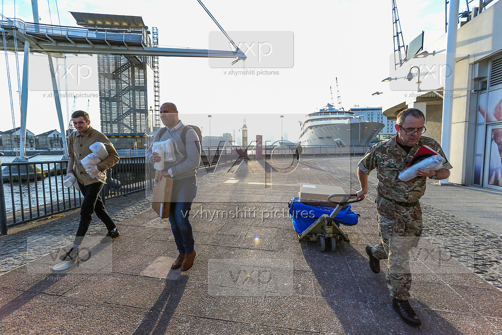 A British Army soldier accompanied by two civilians pulling a cart with medical supplies is seen outside the ExCell Center in London, Thursday, March 26, 2020. The British Government announced Tuesday, that the ExCel Center in east London will become a 4,000 bed temporary hospital to deal with future coronavirus patients, to be called NHS Nightingale. The new coronavirus causes mild or moderate symptoms for most people, but for some, especially older adults and people with existing health problems, it can cause more severe illness or death