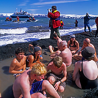 Tourists soak in a hot spring on Deception Island near Antarctica. In the background zodiac rafts shuttle passengers back and forth from the ship,   Clipper Adventurer.