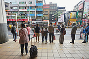 People line up at a bus stop in suburban Taipei.